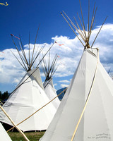 3 white native American tepees against blue sky with coulds